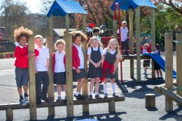 School children at break time playing on climbing frame with teacher
