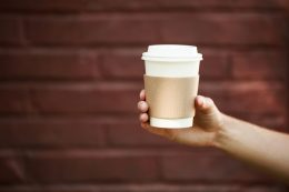 Paper cup of takeaway coffee in the hand